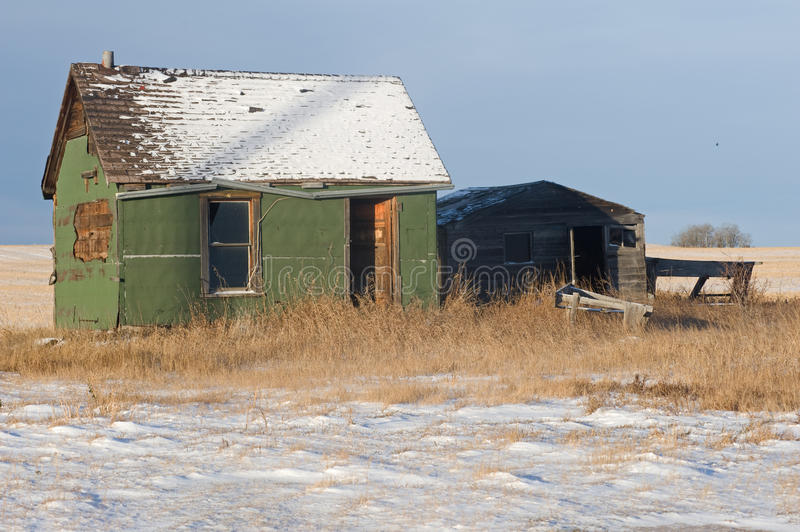 Abandoned old sheds and farm machine in winter stock images