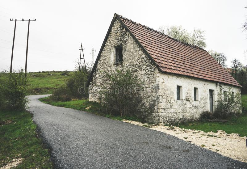 Abandoned old stone rural house. Village house. Derelict haunted stone house and dirt road in the woods. Tree white blossom. Historic, countryside, building stock images
