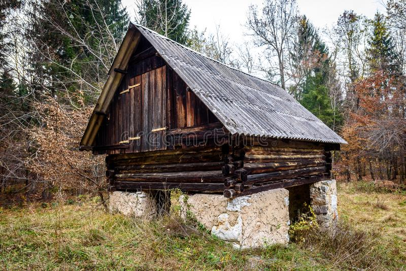 Abandoned old wooden house Cabin in the woods in Slovenia. View of old weathered wooden and stone shepherd cottage stock photography