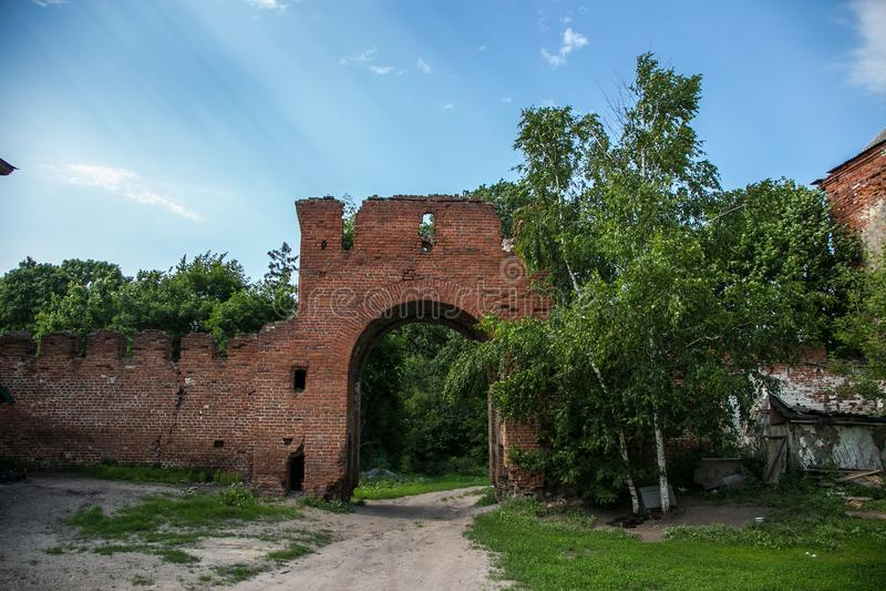 Abandoned and overgrown gateway of red brick to former Kikin Ermolov`s manor, Ryazan region, Russia. Abandoned and overgrown gateway of red brick to former Kikin stock photography