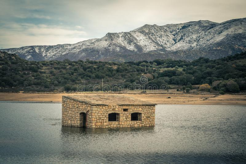 Abandoned and partially submerged stone building in lake in Corsica. Partially submerged abandoned stone building in Lac de Codole lake in the Balagne region of stock image