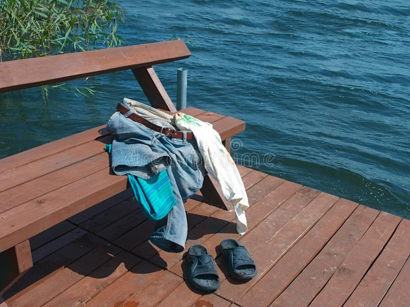 Abandoned personal belongings on beach. A bench on a jetty with abandoned personal belongings, outdoor shot royalty free stock images