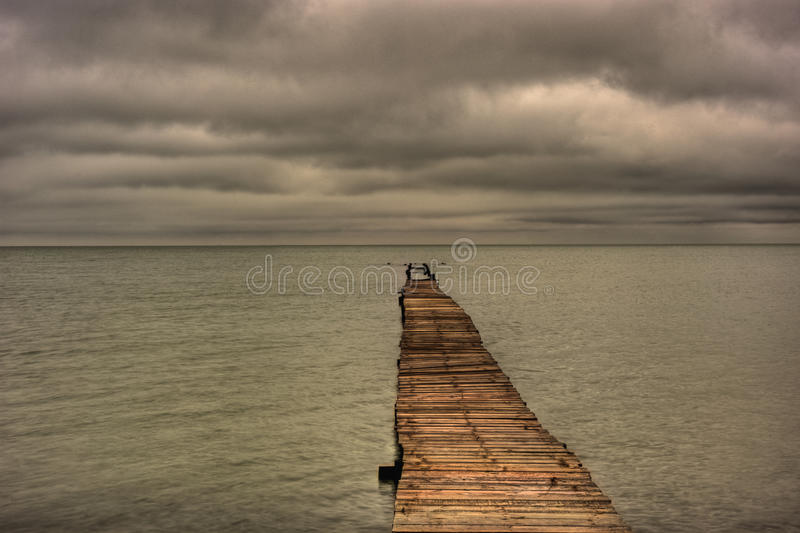 Abandoned Pier Stretching Out Into The Gulf of Mexico. Abandoned wooden plank pier stretching out into the Gulf of Mexico photographed off the Texas Coast stock images