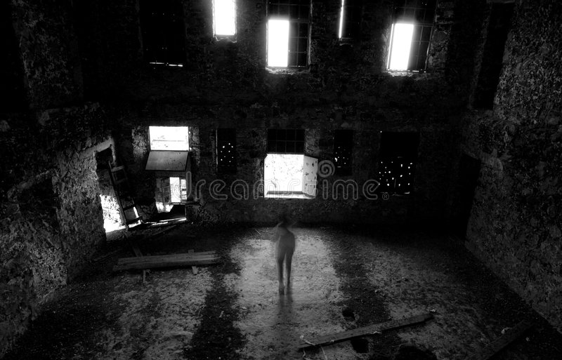 Abandoned place. With open windows and a man standing like a ghost royalty free stock image