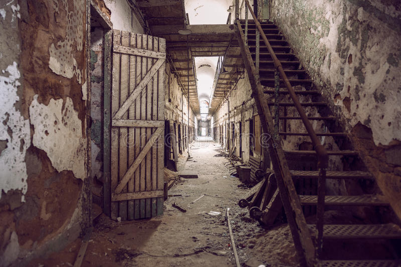 Abandoned prison cell walkway with old rusty stairs, doors and peeling walls. stock photos