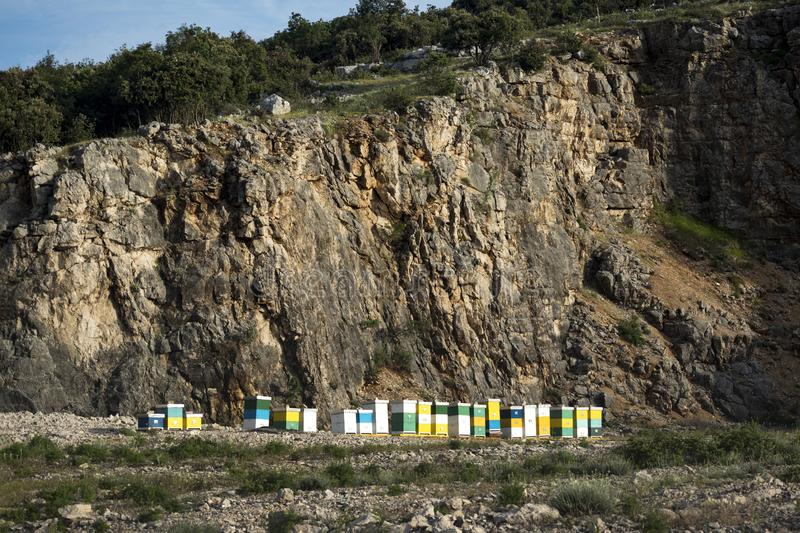 Abandoned quarry with colorful boxes. Honey colorful beehives in a row in nature on the island Brac in Croatia stock photo