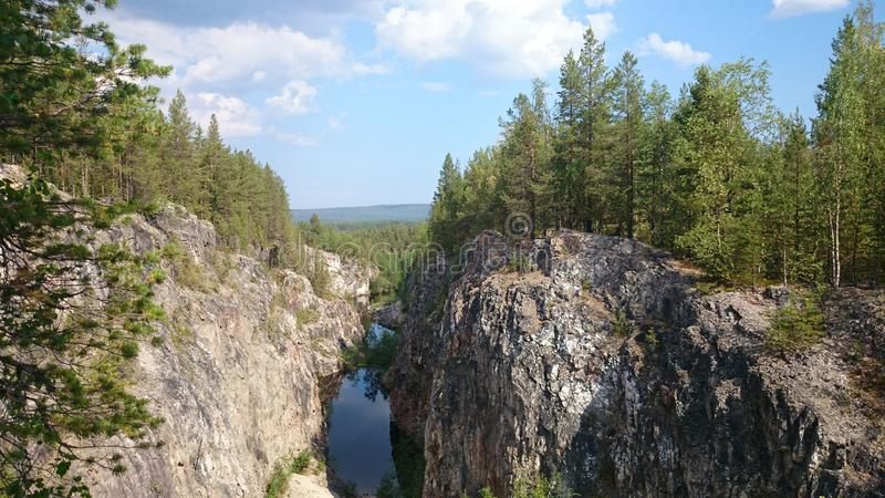 Abandoned quarry. View from the highest rock. A large canyon is filled with water. A pine forest covers its steep slopes stock photos
