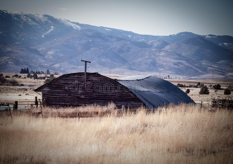 Abandoned Quonset Shed in a Field. An abandoned Quonset shed sits in a golden Autumn field surrounded by the countryside, farmlands, and mountains. Vintage farm royalty free stock photo