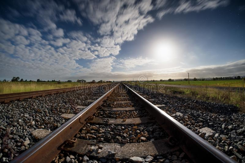 Abandoned railway track lighted by moonlight royalty free stock image