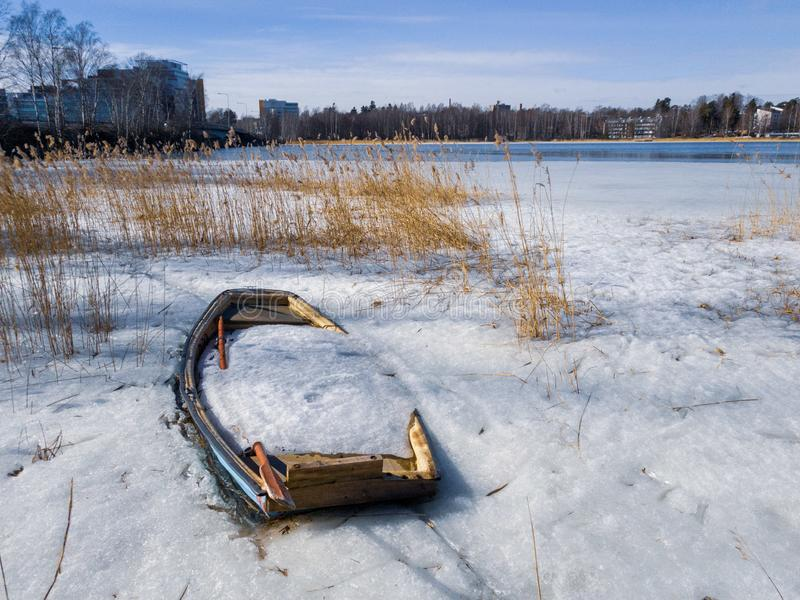 Abandoned rowing boat full of ice and snow stock photo