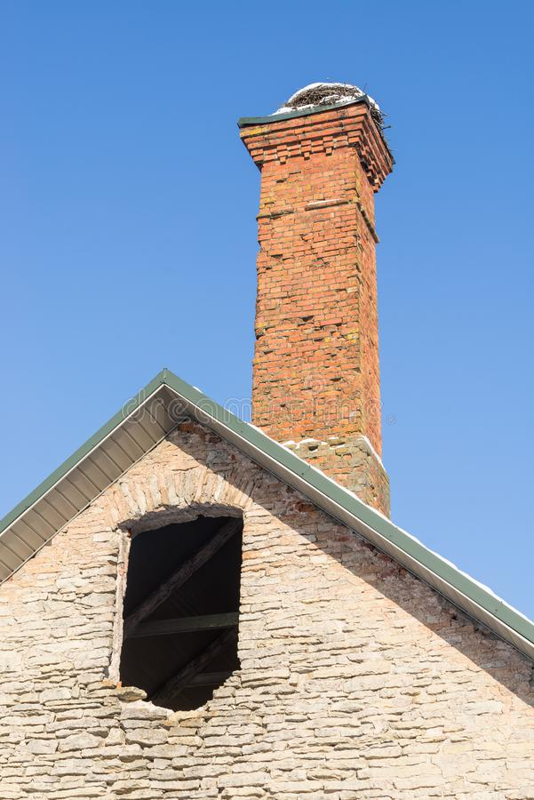 Abandoned ruin of oven chimney. Broken furnace. Snowy roof, stork slot and blue sky background in the winter. stock photo