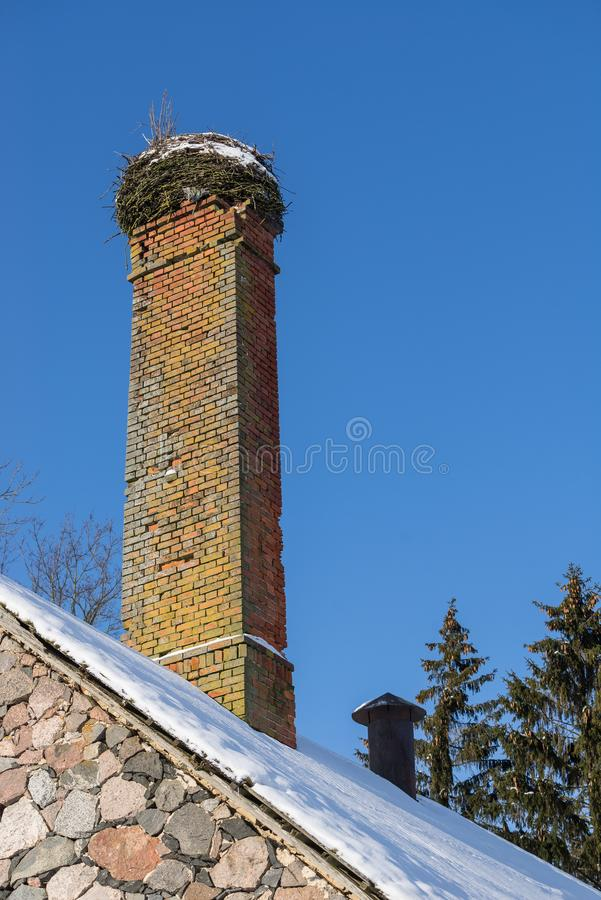 Abandoned ruin of oven chimney. Broken furnace. Snowy roof, stork slot and blue sky background in the winter. royalty free stock photos