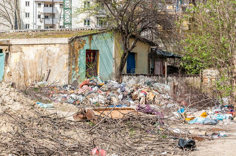 Abandoned rural damaged house in the ghetto near new residential building in the city used as garbage dump with junk and litter in stock photography