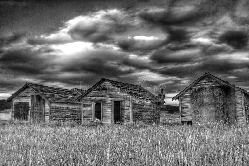 Abandoned Rustic Living Quarters. Some abandoned rustic living quarters in black and white with a dramatic sky in the background and a grassy field in the stock image