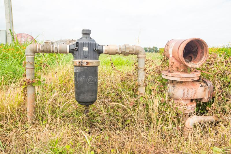 Abandoned Rustic Water Pipe and Water Filter in Field royalty free stock photo