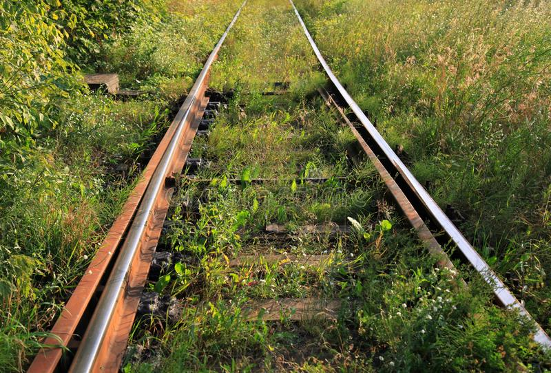 Abandoned rusty and active railway track overgrown with grass stock images