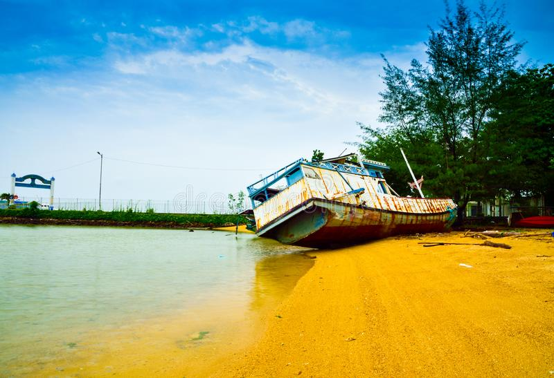 Abandoned rusty fisherman boat on the sandy beach royalty free stock photography