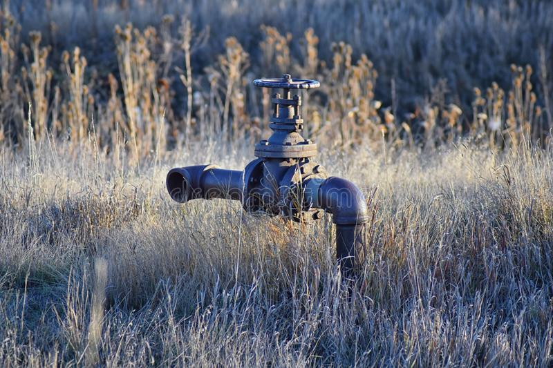Abandoned rusty irrigation pipe to nowhere against tall grass in the Cradleboard Trail walking path on the Carolyn Holmberg Preser royalty free stock images