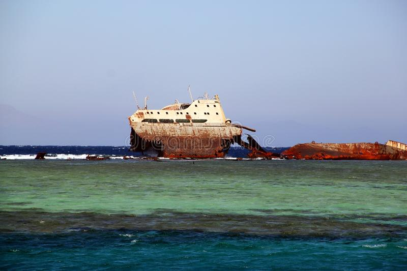 Abandoned rusty ship in blue sea waves stock image