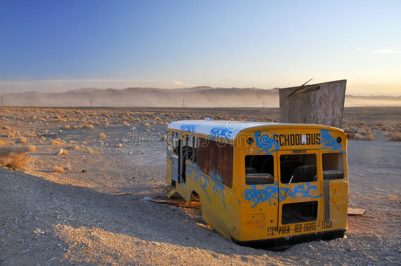 Abandoned school bus. Broken abandoned school bus in sandy desert stock image