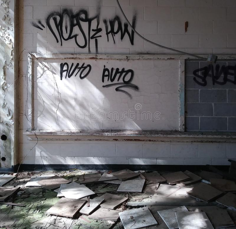 Abandoned School Classroom and Graffiti. Background, backgrounds, backdrop, tagging, wall, shadow, light, grungy, grunge, building, blackboard, chalkboard stock image