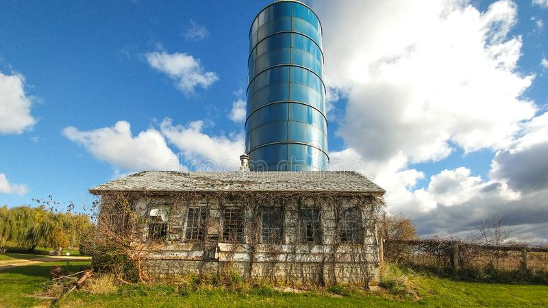 Abandoned Shed with Blue Silo on a Farm stock photography