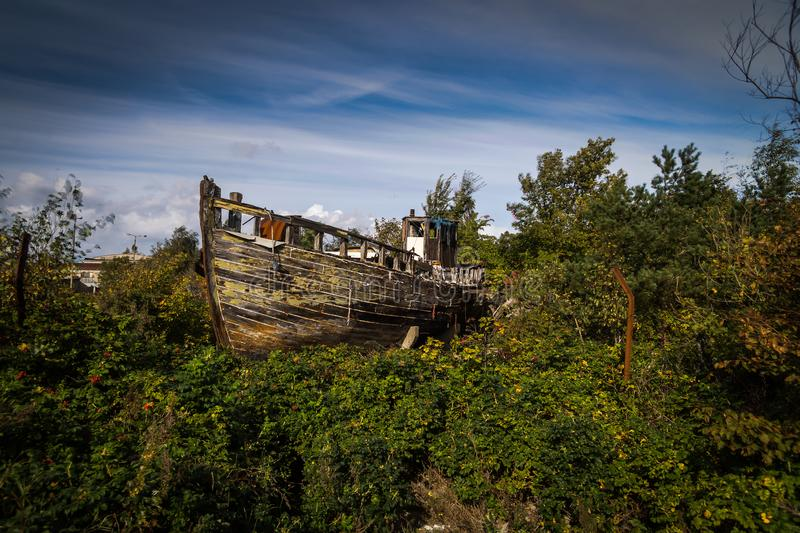 Abandoned ship wreck in the grass and pines on Hel peninsula in Poland. Abandoned wooden ship wreck in the green grass and pines on Hel peninsula in Poland with stock images