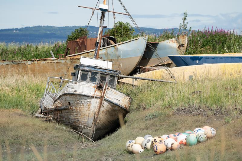 Abandoned shipwreck in a boat graveyard in Homer Spit Alaska. On a sunny day stock photos