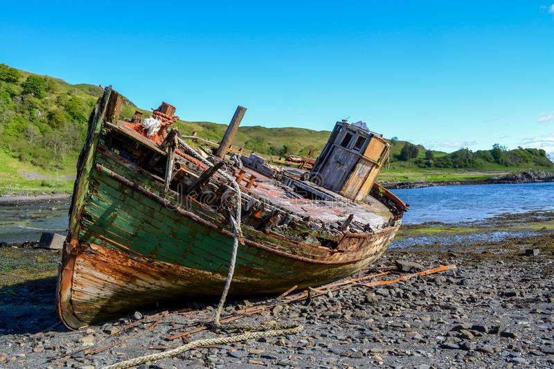 Abandoned shipwreck of an old fishing boat. An abandoned shipwreck of an old fishing boat lying on the beach of the Scottish Isle of Kerrera royalty free stock photography