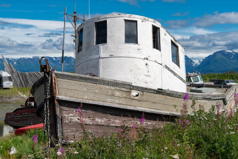 Abandoned shipwreck sits in a junkyard along the Homer Spit. In Alaska on a sunny day royalty free stock photo