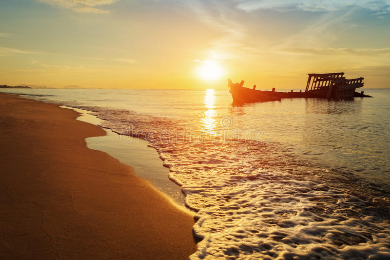Abandoned shipwreck of wood fishing boat. On beach at Twilight time royalty free stock image