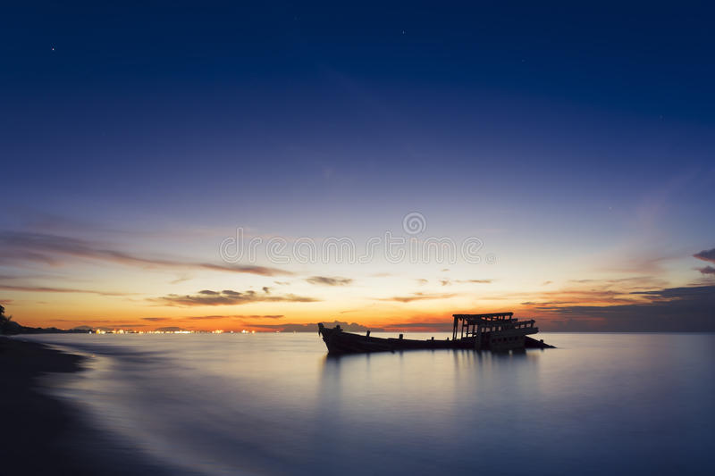 Abandoned shipwreck of wood fishing boat. On beach at Twilight time stock image