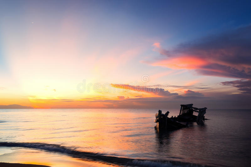 Abandoned shipwreck of wood fishing boat. On beach at Twilight time stock images