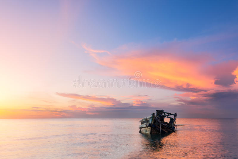 Abandoned shipwreck of wood fishing boat. On beach at Twilight time royalty free stock photo