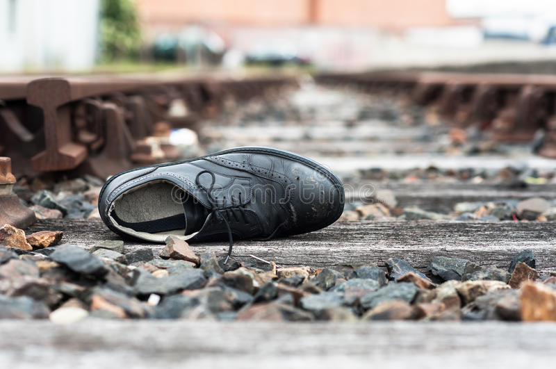 Abandoned shoe on train tracks. A single abandoned and scuffed formal shoe lying on train tracks royalty free stock photos