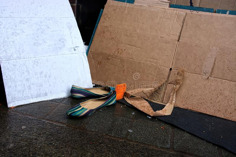 Abandoned shoes. Homelessness. A pair of shoes left at the site of a homeless persons cardboard bedding used to insulate themselves against the cold and wet royalty free stock photography