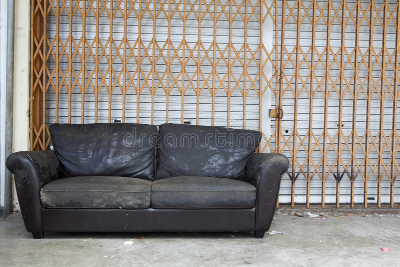 Abandoned shop. With weathered worn couch in front stock images