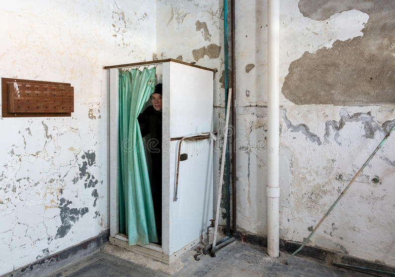 Abandoned shower and man inside Trans-Allegheny Lunatic Asylum. Senior man emerges from shower stall and curtain inside Trans-Allegheny Lunatic Asylum in Weston royalty free stock photography