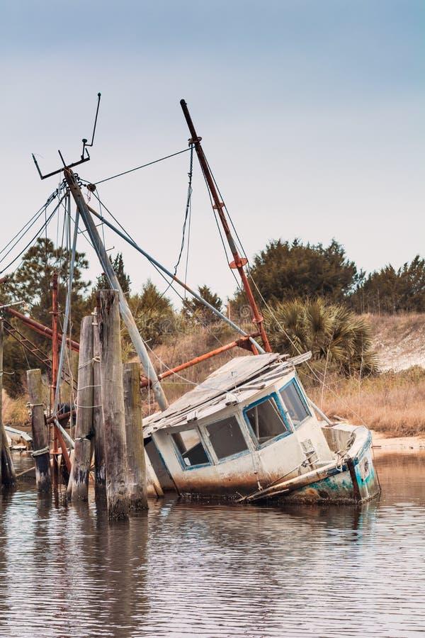 Abandoned shrimp boat half sunk stock photo