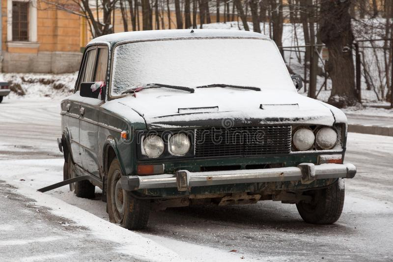 Abandoned snowy old car on a city street stock image