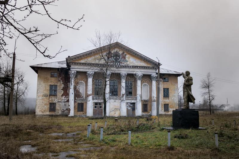 Abandoned Palace of culture of Stalin`s construction with Lenin monument in the foreground stock images