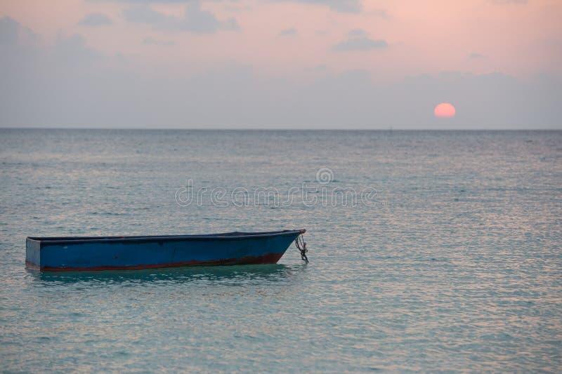 Abandoned submerged woooden boat. Abandoned submerged boat at sunset in Maldives stock photos