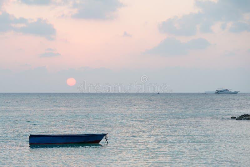 Abandoned submerged woooden boat. Abandoned submerged boat at sunset in Maldives royalty free stock photos