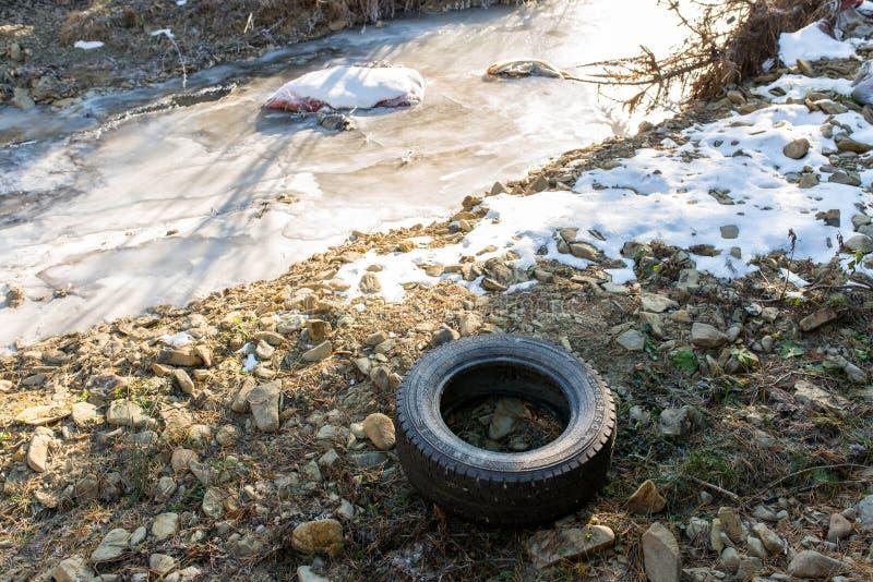 Abandoned tire near a frozen little creek, conceptual image of human negligence. Bancu, Romania-01 December 2018: Abandoned tire near a frozen little creek stock photos