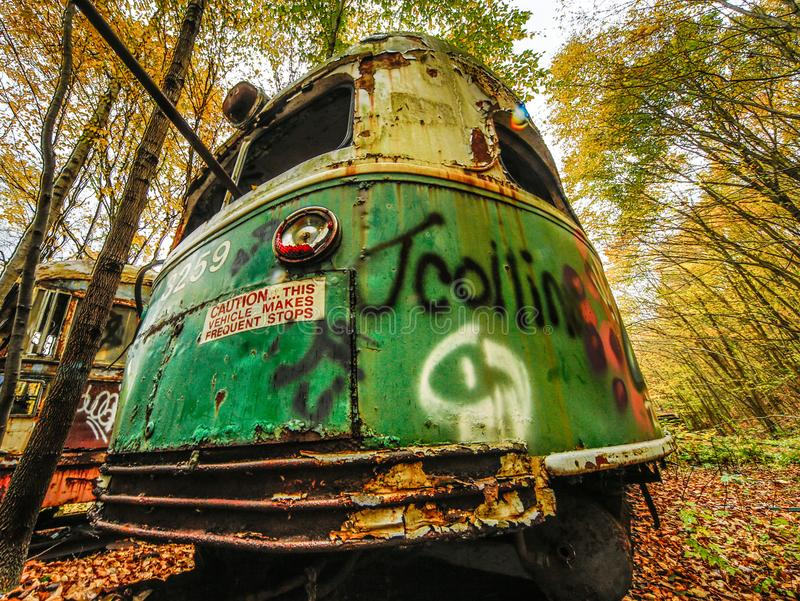Abandoned Trolley Car in Woods in Fall with Caution Sign. And graffiti and broken windows and rust with green paint royalty free stock image