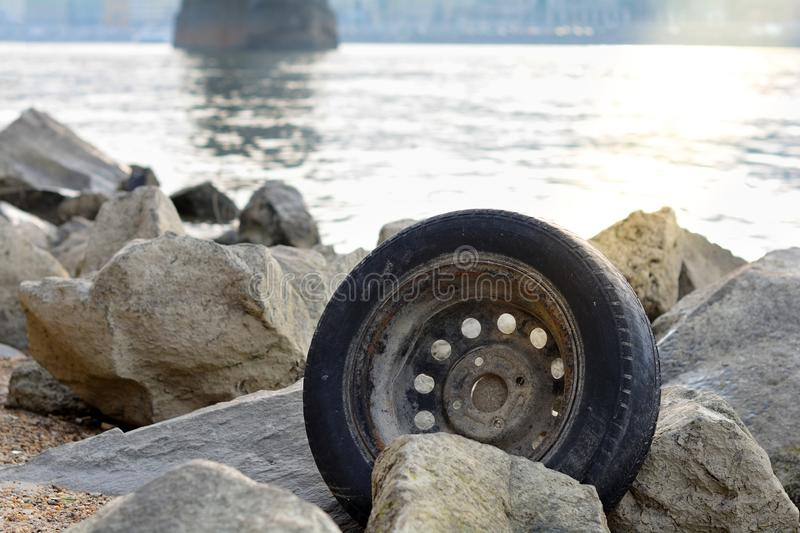 Abandoned used tyre on coastline. The problem of recycling waste, garbage, environmental pollution. Car tire thrown on the beach. stock images