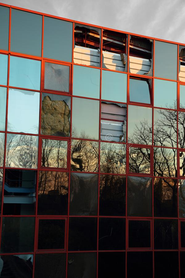 Abandoned vandalized glass fronted office building. With trees reflected royalty free stock image