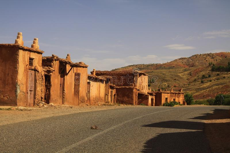 Abandoned village of clay houses along empty road in Atlas mountains, Morocco. Abandoned village of clay houses along empty road in Atlas mountains stock photos