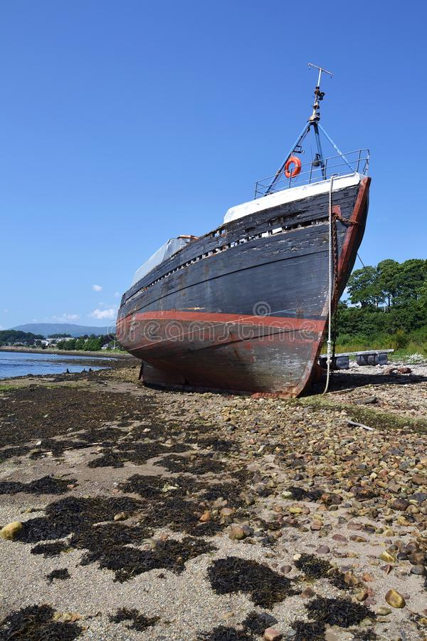 Abandoned vintage fishing boat on beach near Corpach village, Fort William, Scotland, United Kingdom stock images