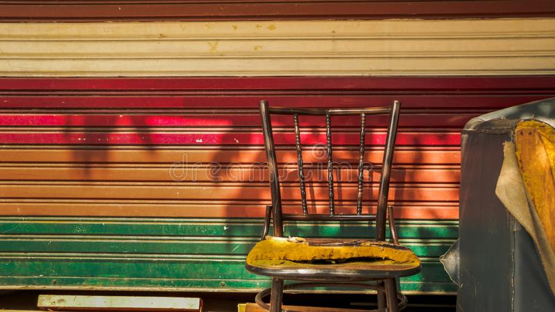 Abandoned Vintage Metal Chair and Couch/ Sofa with Colorful Roll. Er Shutter Door/ Corrugated Iron Background. Outdoor Garage/ Junkyard. Street Photography royalty free stock photos